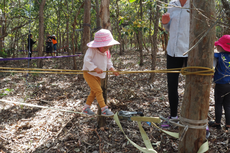 Young girl crossing a slackline with ropes handlines in a forest.