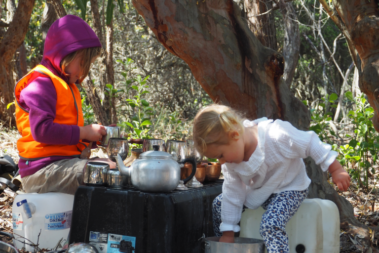 Two young girls playing with tea cups and kettles