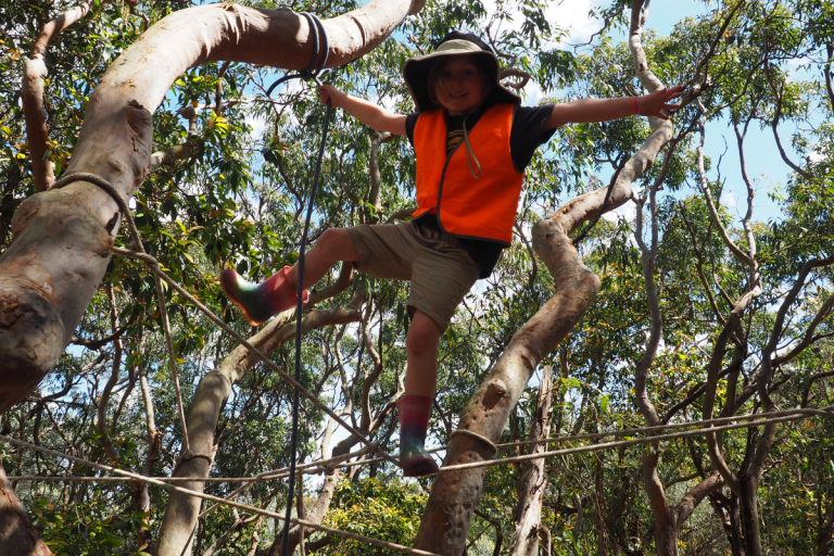 Young girls climbing ropes in a tree